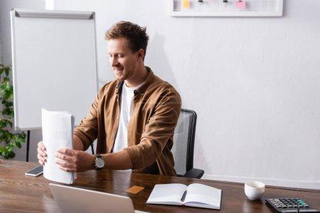 Enfoque selectivo del empresario que sostiene documentos cerca de dispositivos digitales y café en el lugar de trabajo