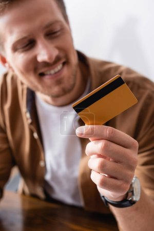 Selective focus of businessman holding credit card at table