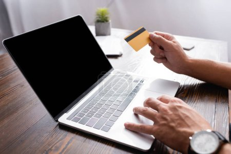 Cropped view of businessman using laptop and credit card at table in office