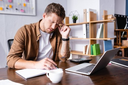 Photo pour Selective focus of pensive businessman writing on notebook beside cup of coffee, laptop and calculator on table - image libre de droit