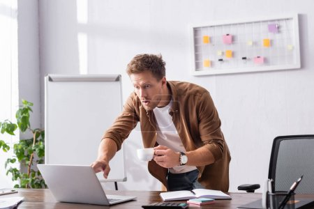 Selective focus of excited businessman with cup of coffee looking at laptop in office