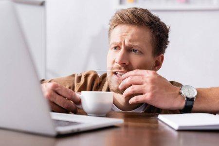 Selektiver Fokus des fokussierten Geschäftsmannes mit einer Tasse Kaffee, der auf den Laptop am Tisch blickt
