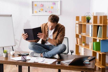 Joven empresario que trabaja con cuaderno y papeles cerca de dispositivos digitales en la mesa