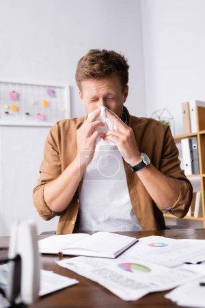 Photo pour Concentration sélective de l'homme d'affaires malade tenant la serviette près du nez dans le bureau - image libre de droit