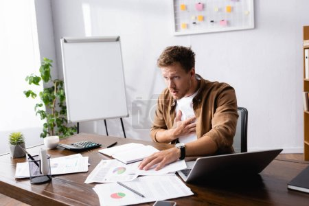 Photo pour Selective focus of businessman touching chest while feeling hurt in office - image libre de droit