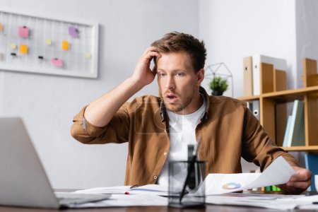 Selective focus of shocked businessman holding document and looking at laptop in office