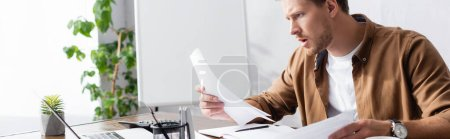 Photo pour Horizontal crop of focused businessman looking at papers at table in office - image libre de droit