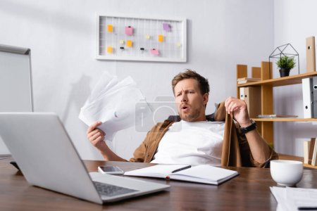 Photo for Selective focus of businessman holding documents while suffering from heat in office - Royalty Free Image