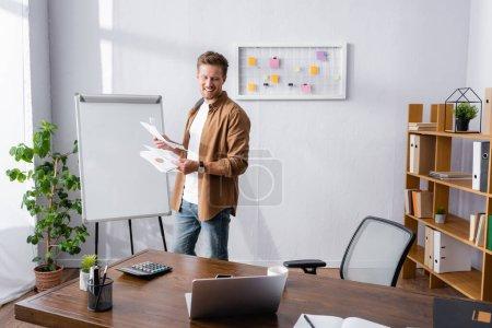 Selektiver Fokus von Geschäftsleuten, die Papiere in der Nähe von Laptop und Taschenrechner auf dem Bürotisch halten
