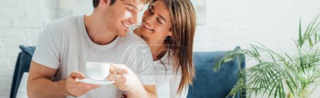Horizontal crop of woman looking at boyfriend with cup of coffee