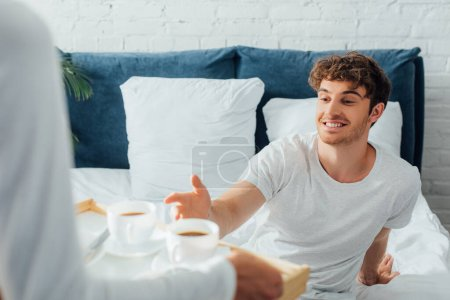 Photo for Selective focus of man sitting on bed near girlfriend with coffee cups on breakfast tray - Royalty Free Image