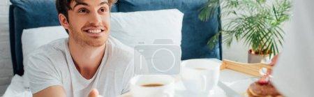Photo pour Image horizontale de l'homme assis sur le lit près de la femme avec petit déjeuner sur plateau le matin - image libre de droit
