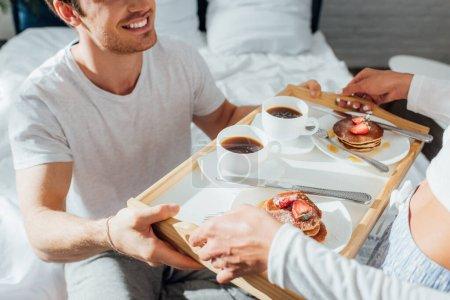 Photo pour Vue recadrée d'un jeune couple en pyjama tenant un plateau de petit déjeuner avec crêpes et café au lit - image libre de droit