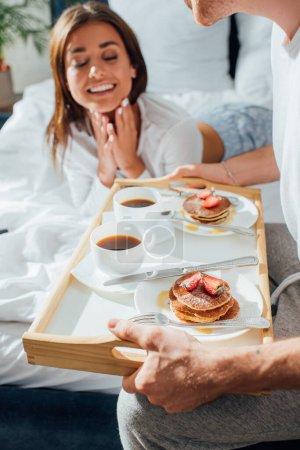 Mann frühstückt selektiv auf Tablett neben Frau im Bett