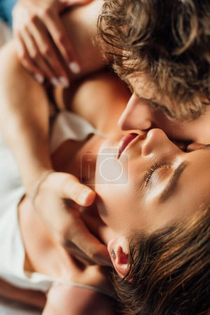 Selective focus of man kissing girlfriend with closed eyes