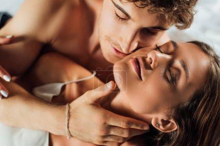 Photo pour Focus sélectif d'un homme torse nu touchant le cou et embrassant une jeune femme - image libre de droit