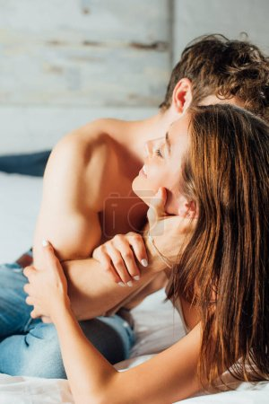 Photo for Selective focus of young shirtless man touching face of girlfriend on bed - Royalty Free Image