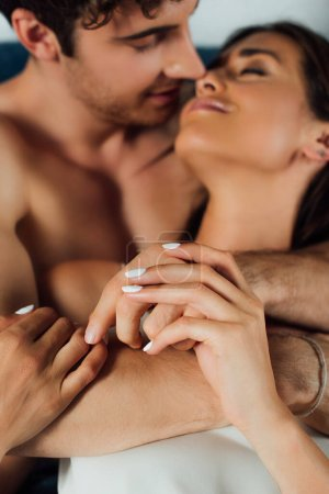 Concentration sélective du jeune couple se tenant la main à la maison
