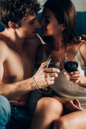 Selective focus of shirtless man clinking wine with sensual girlfriend at home