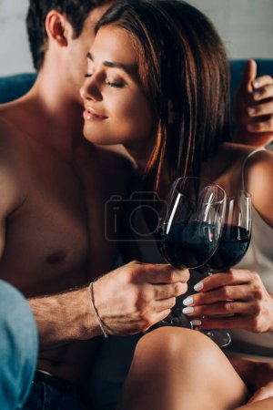Selective focus of young woman holding glass of wine near shirtless man