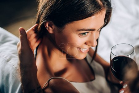 Photo for Selective focus of man touching hair of girlfriend with glass of wine on bed - Royalty Free Image