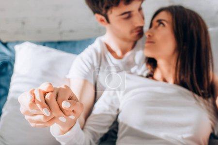 Photo pour Foyer sélectif de jeune couple tenant la main et se regardant sur le lit - image libre de droit