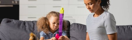 Photo pour Image horizontale de la jeune nounou afro-américaine en t-shirt rayé près de tour de construction fille de blocs multicolores - image libre de droit