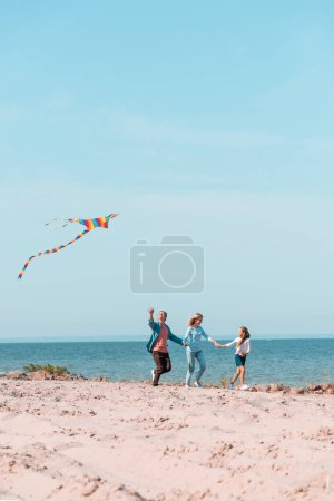 Photo pour Selective focus of family holding hands while running with kite on beach near sea - image libre de droit