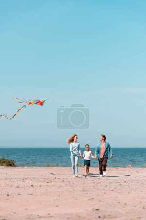 Photo for Selective focus of woman with kite walking near daughter and husband on beach - Royalty Free Image