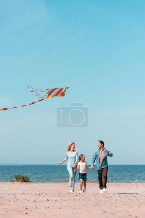 Concentration sélective de la famille courir avec cerf-volant sur la plage pendant les vacances près de la mer