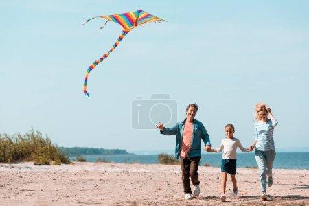 Photo pour Famille avec fille et cerf-volant courir sur la plage pendant les vacances - image libre de droit
