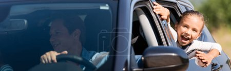 Horizontal concept of excited kid looking through car window near father
