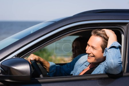 Photo for Selective focus of man driving car near wife during weekend - Royalty Free Image