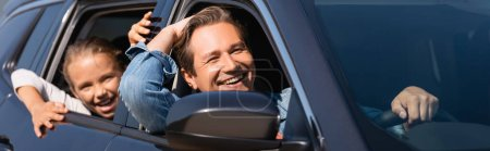 Panoramic shot of man driving car near excited daughter