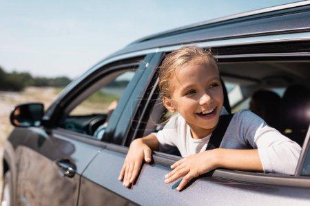 Selective focus of kid looking away through car window