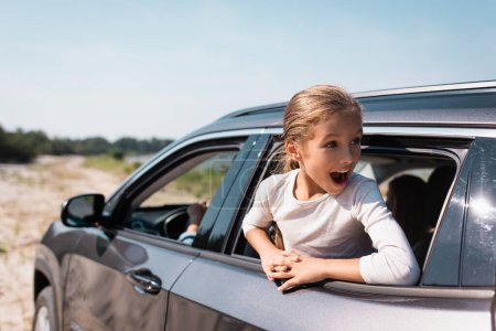 Selective focus of shocked child looking away while traveling in car with parents