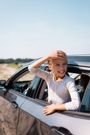 Selective focus of child with hand near head looking through car window during vacation with parents