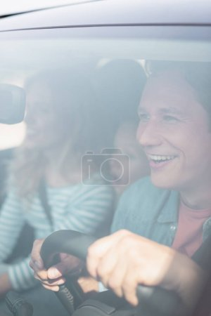 Photo for Selective focus of excited man driving car near family - Royalty Free Image
