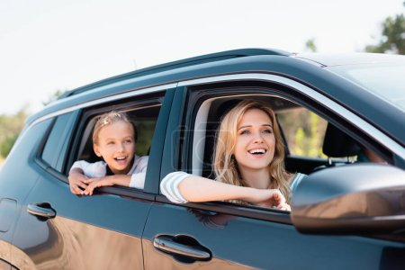 Selective focus of excited mother and kid looking away while traveling in auto