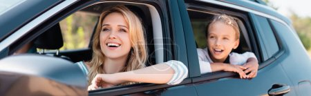 Panoramic shot of excited woman looking away while traveling with daughter in car