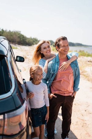 Photo for Selective focus of woman embracing husband near daughter and auto on beach - Royalty Free Image