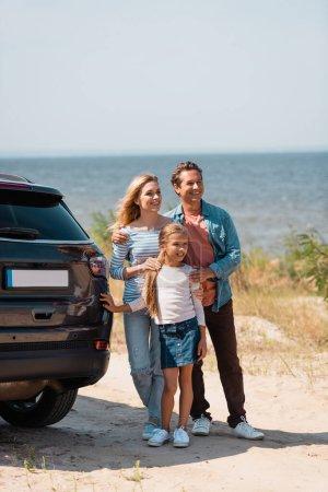 Selective focus of parents hugging daughter near auto on beach near sea
