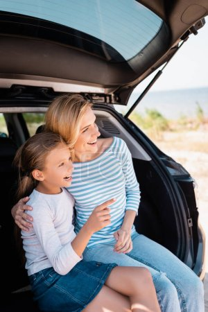 Photo for Daughter pointing with finger while sitting near mother in car trunk - Royalty Free Image