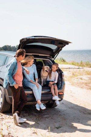 Photo pour Concentration sélective des parents regardant la fille avec golden retriever dans le coffre de la voiture sur la plage - image libre de droit