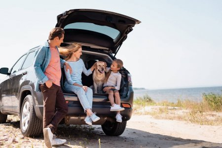 Photo for Selective focus of family with golden retriever traveling on car on beach - Royalty Free Image