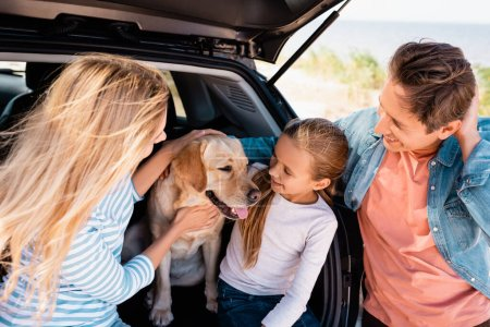 Photo for Selective focus of family looking at golden retriever in car truck outdoors - Royalty Free Image