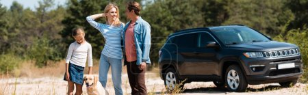 Photo pour Horizontal image of family with daughter and golden retriever standing near car during vacation - image libre de droit