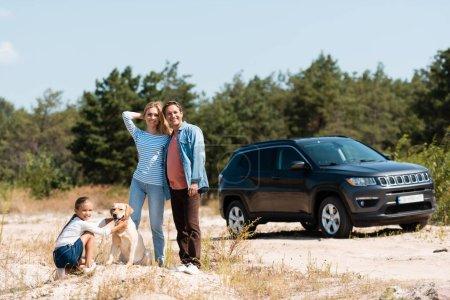 Photo pour Foyer sélectif de l'homme étreignant femme près de la fille avec golden retriever pendant les vacances - image libre de droit