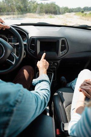 Ausgeschnittene Ansicht eines Mannes, der mit dem Finger zeigt, während er Auto in der Nähe seiner Frau fährt