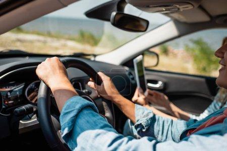Mann fährt mit digitalem Tablet Auto neben Frau